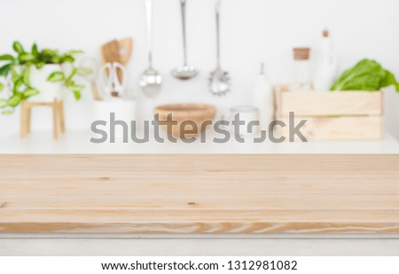 Wooden table top over blurred kitchen utensils for product display
