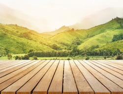 wooden table top with beautiful green landscape and mountain view sunlight in the morning