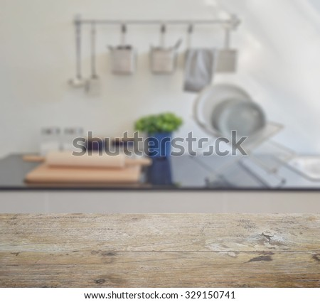 wooden table top with blur of modern ceramic kitchenware and utensils on the counter top