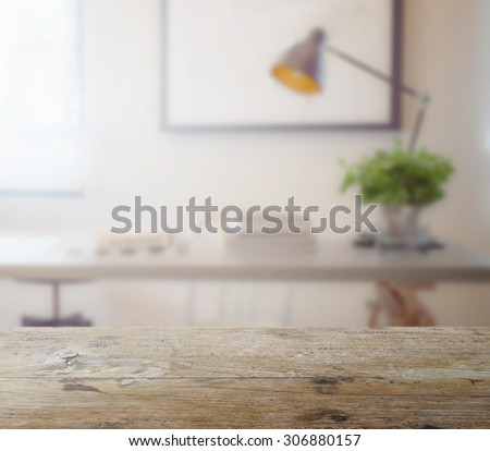 wooden table top with blur of modern working table with book and lamp as background #306880157
