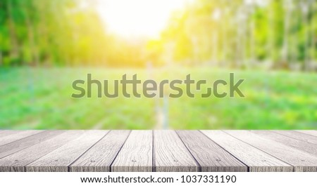 Wooden table top with blurred nature background in the morning and sunlight use for products display  #1037331190