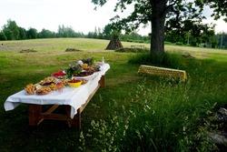 Wooden table under oaks with many traditional Latvian food. Old Latvian culture tradition LIGO. Midsummer night celebrating in Latvia.