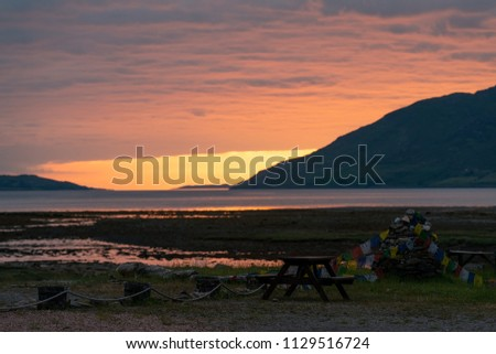 Wooden table with banks and a flags decoration with dramatic sunset  in a small village of Garve, Scotland