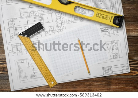 Wooden table with blueprints, a ruler with angle bar, a builders level, a pencil and cross section paper lying on it. Design and engineering. Building and construction. Professional workplace.