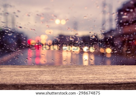 wooden table with blur traffic view through a car windscreen covered in rain for background