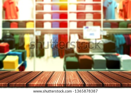 Wooden table with blurry background of casual boutique shop, shirt brand outlet or colorful clothes store for product display montage. Retail business of fashion product for online marketing backdrop.