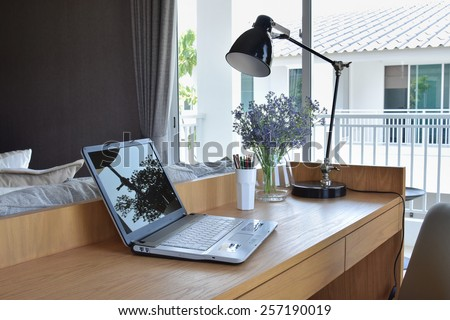 wooden table with computer notebook,pencil,lamp and artificial flowers in modern working area at home #257190019