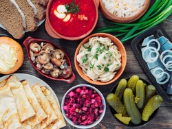 Wooden table with dishes of russian cuisine - borscht, pelmeni, herring, marinated mushrooms, salted cucumbers, vinaigrette, sauerkraut, rye bread, pancakes, cheese pastry. Russian food. Top view