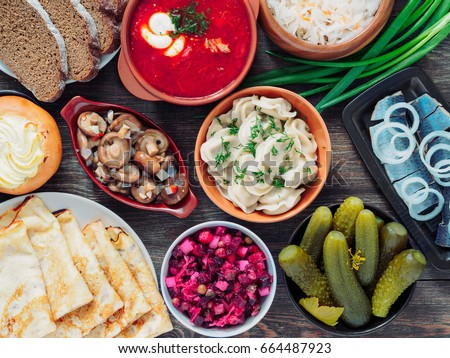 Wooden table with dishes of russian cuisine - borscht, pelmeni, herring, marinated mushrooms, salted cucumbers, vinaigrette, sauerkraut, rye bread, pancakes, cheese pastry. Russian food. Top view #664487923