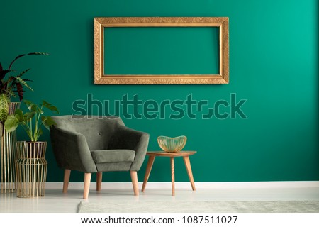 Wooden table with gold, metal bowl standing by a green armchair in living room interior with frame on the wall #1087511027