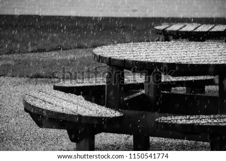 Wooden table with seats under a downpour. Sad and romantic, monochromatic picture.  #1150541774