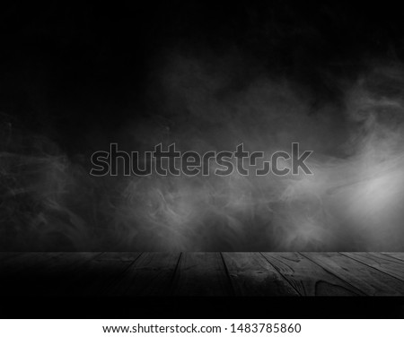 Wooden table with smoke and black backgrounds