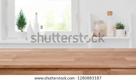 Wooden tabletop in front of blurred kitchen window, shelves background Stockfoto ©