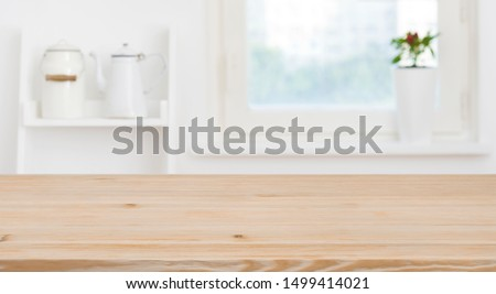 Wooden tabletop in front of blurred kitchen window, shelves background