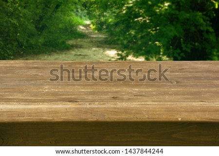Wooden tabletop with a thick tabletop in perspective with forest on background #1437844244
