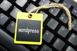 wooden tag written Wordpress over keyboard button background