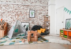 Wooden take-apart playhouse and play tent in interior of children's room