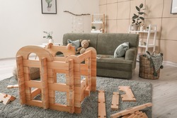 Wooden take-apart playhouse in interior of room