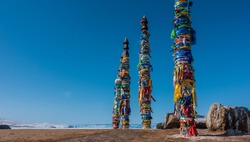 Wooden tall pillars, standing in a row, are tied with multi-colored ritual ribbons. Nearby, on the ground, there are picturesque boulders. Clear blue sky. Mount Shamanka. Baikal