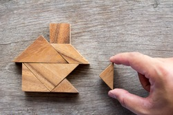 Wooden tangram puzzle wait to fulfill home shape for build dream home, happy life, house or mortgage investment concept