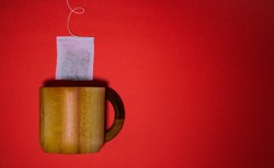 Wooden tea cup and tea bag, overhead shot, on a red background. Hot and cold drinks