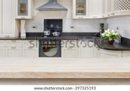 Wooden textured table over blurred kitchen interior background
