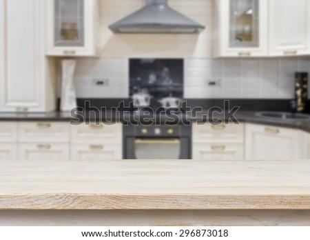 Wooden textured table over blurred kitchen vintage interior background