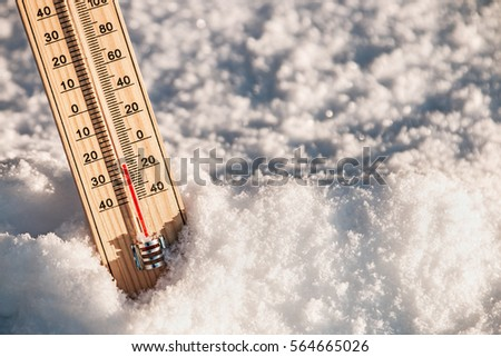 Wooden Thermometer in the snow with freezing temperatures #564665026