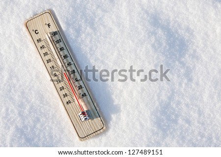 wooden thermometer in the snow with zero temperature