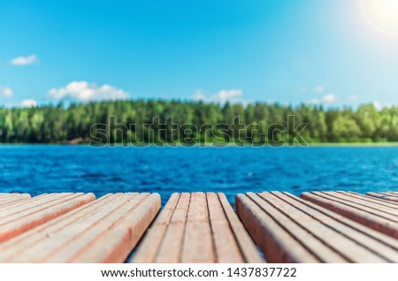 Wooden timber of a rural mooring on a lake in the middle of the forest. A peaceful river dock in the woods.Sunny footbridge. Minimal background with blue sky,clean lake and mooring in the country side