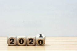 Wooden 2020 to 2021 new year white background.  Word 2020 & 2021 wood cube on wooden desk for copy space.