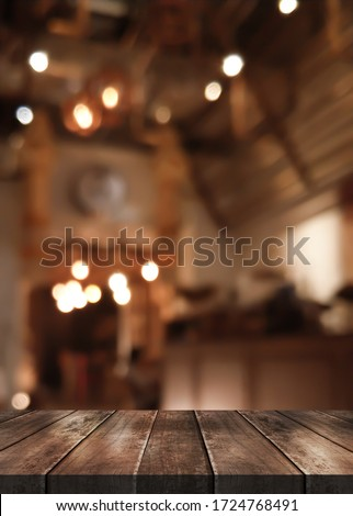 Wooden top table with bokeh light effect and blur restaurant on background, blur background.