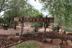 Wooden tourist information signboard of Kruger Gate at entrance gate of traditional african Kruger National Park, tourism landmark attraction with scenic wildlife and wild animals in South Africa.