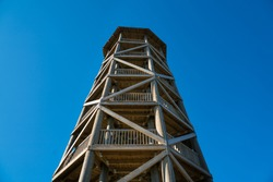 Wooden tower in Kolga Aabla swamp national park. Watch tower in raised bog. View platform with amazing blue sky. Tall tower - high view point in Estonian swamp. Timber construction. Timber sky scraper