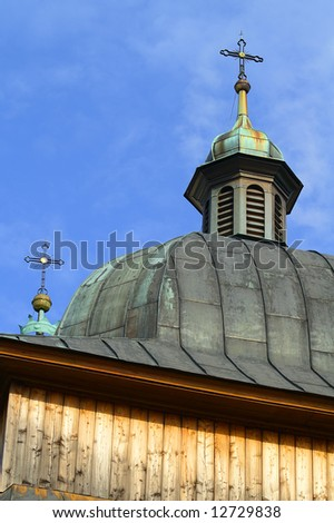 wooden tower of the historic church against cloudy, blue sky