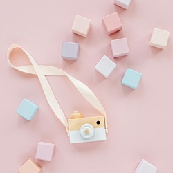 Wooden toy camera and colorful toy blocks. Stylish baby toys on pastel pink background. Eco friendly, plastic free toys accessories for kids. Flat lay, top view