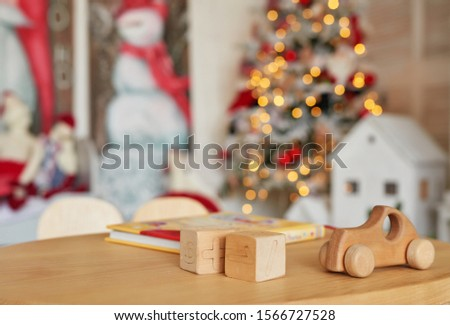 Wooden toy car and cubes, natural wood toy, shape of colored wooden, Baby toy, toys set for babies. New Year's Christmas card template. Stylish Scandinavian children's room with a Christmas tree.