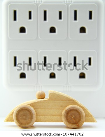 Wooden, toy car in front of a multi-electrical outlet adapter.