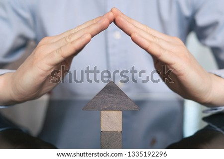 Wooden toy house protected by hands. The concept of buying and selling real estate, rental housing, Home protection, Home protection #1335192296