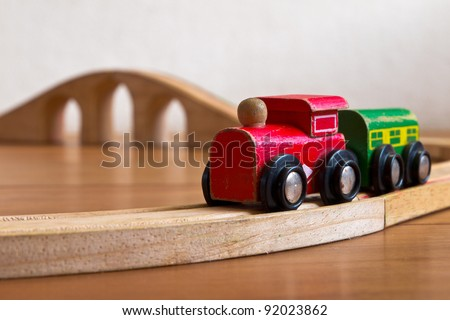 Wooden toy train on railroad with bridge in backdrop