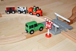 Wooden toy train. Rail crossing scene. Train with driver runs on a wooden track system with grooves to guide the wheels of the rolling stock. Car stopped by the barrier before the railway crossing.