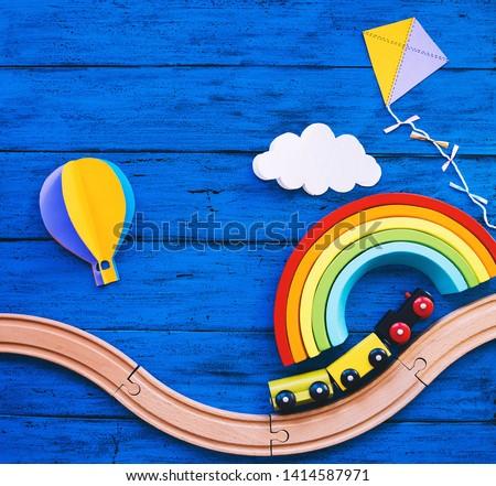 Wooden toy train, railway for preschool child, wood rainbow, paper crafts on blue table. Waldorf or montessori school background. Kids dream, travel concept. Educational toys for kindergarten children