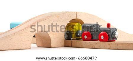 Wooden toy train under bridge isolated on white