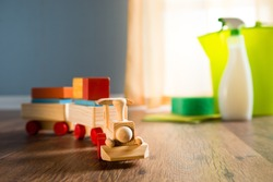 Wooden toy train with cleaning products on background next to a window.