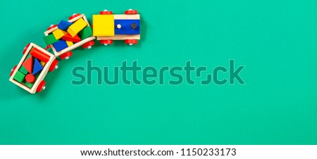 Wooden toy train with colorful blocks on green background #1150233173