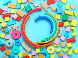 Wooden toys on blue background with blank space for text. Top view, flat lay.