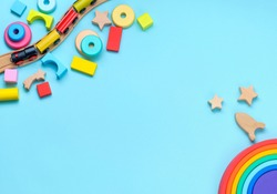 Wooden toys rainbow, train and blocks on blue background with blank space for text. Top view, flat lay.