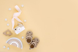 Wooden toys with rainbow, toy camera and cute baby slippers for kids on yellow background.  Set of gender neutral newborn accessories. Flat lay, top view