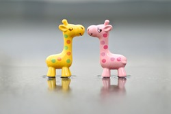 Wooden toys yellow and pink giraffe photographed with the effect of puddles and blurred background. Close up photo.