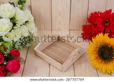 Wooden tray and rose on wood texture.